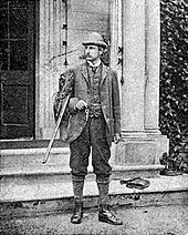 Young Rider Haggard standing at the steps of an English country house with a hunting gun uncocked in his arm
