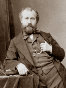 Man in early middle age, slightly balding, with neat moustache and beard, standing facing the viewer