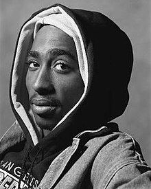A black and white photo of Tupac Shakur staring at the viewer