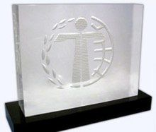 A Humanitas Prize trophy. A crystal sculpture engraved with the stylized image of a child standing with a laurel wreath and a world globe.