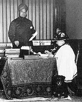 The Munshi stands over Victoria as she works at a desk