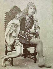 man in 16th century costume sitting in chair