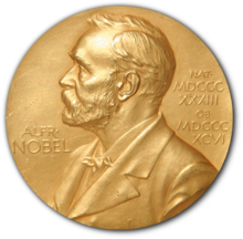 """A golden medallion with an embossed image of a bearded man facing left in profile. To the left of the man is the text """"ALFR•"""" then """"NOBEL"""", and on the right, the text (smaller) """"NAT•"""" then """"MDCCCXXXIII"""" above, followed by (smaller) """"OB•"""" then """"MDCCCXCVI"""" below."""