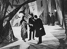 A man shakes hands with a woman, while another man looks on between them. The three figures stand in the iddle of a city street, with brick walls in twisted and distorted shapes, and shadows and streaks of light painted onto the walls and ground.