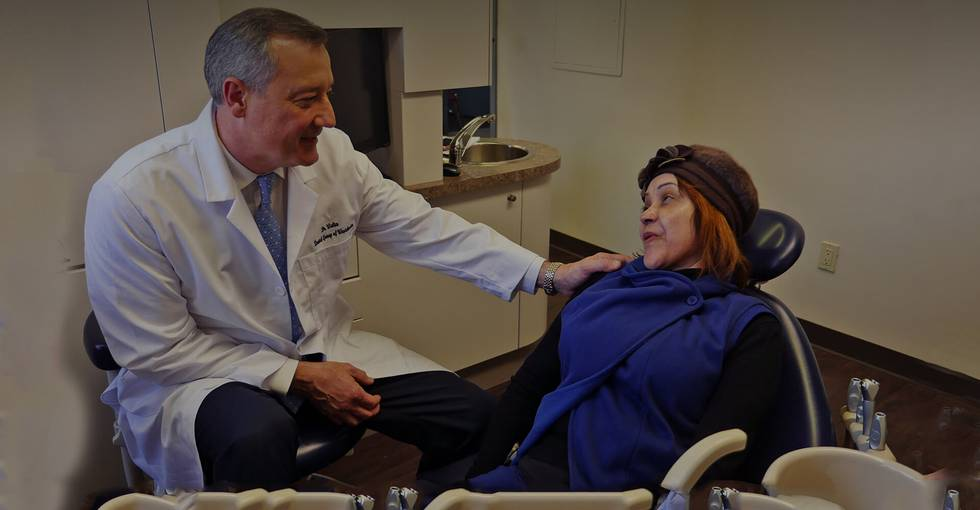 Your Dentist in White Plains NY and a woman sitting on the patient room
