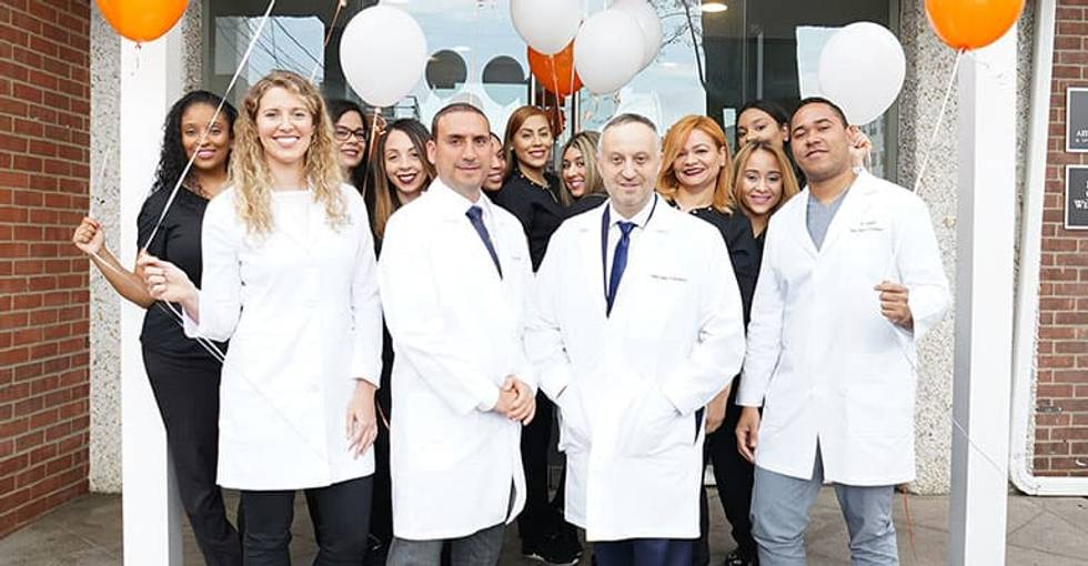 Your dentists in White Plains NY standing with their dental team on the front steps of their office with balloons and smiling faces welcoming you to their dental practice.