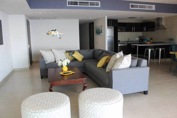 Comfy living room and modern kitchen with fridge, dishwasher, microwave and kitchen utensils