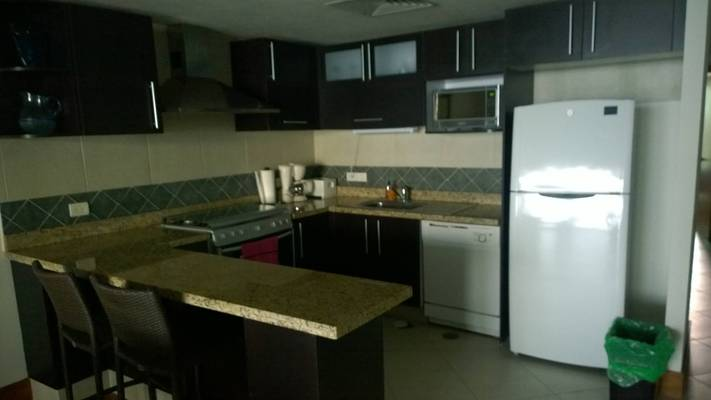 Granite countertop kitchen equipped with refrigerator, freezer, dishwasher, stove top, and oven