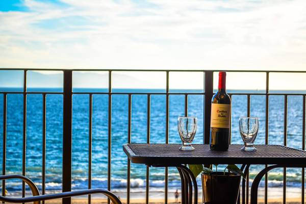 Beautiful outside view of the ocean with wine on the patio table