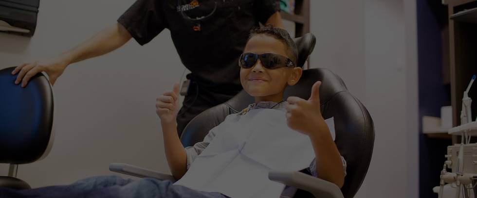 Young kid showing his thumbs up in the dentist chair and wearing glasses